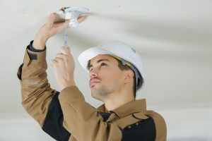 Wright electrician installing ceiling lights.
